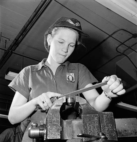 Woman factory worker files a machine part while piped music plays on loudspeakers. flickr.com.photos.lac-bac